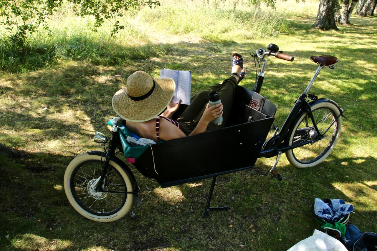 kvinna i hatt läser i lastcykel